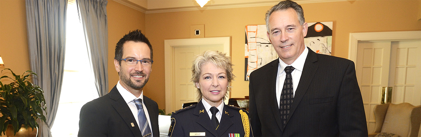 Une photo de la sous-commissaire principale Anne Kelly en uniforme de cérémonie, debout entre Martin Gagnon et Jeremy Mills.