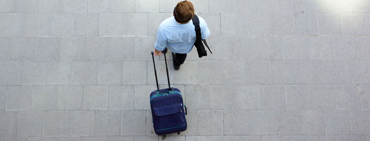 A photo of a man pulling luggage