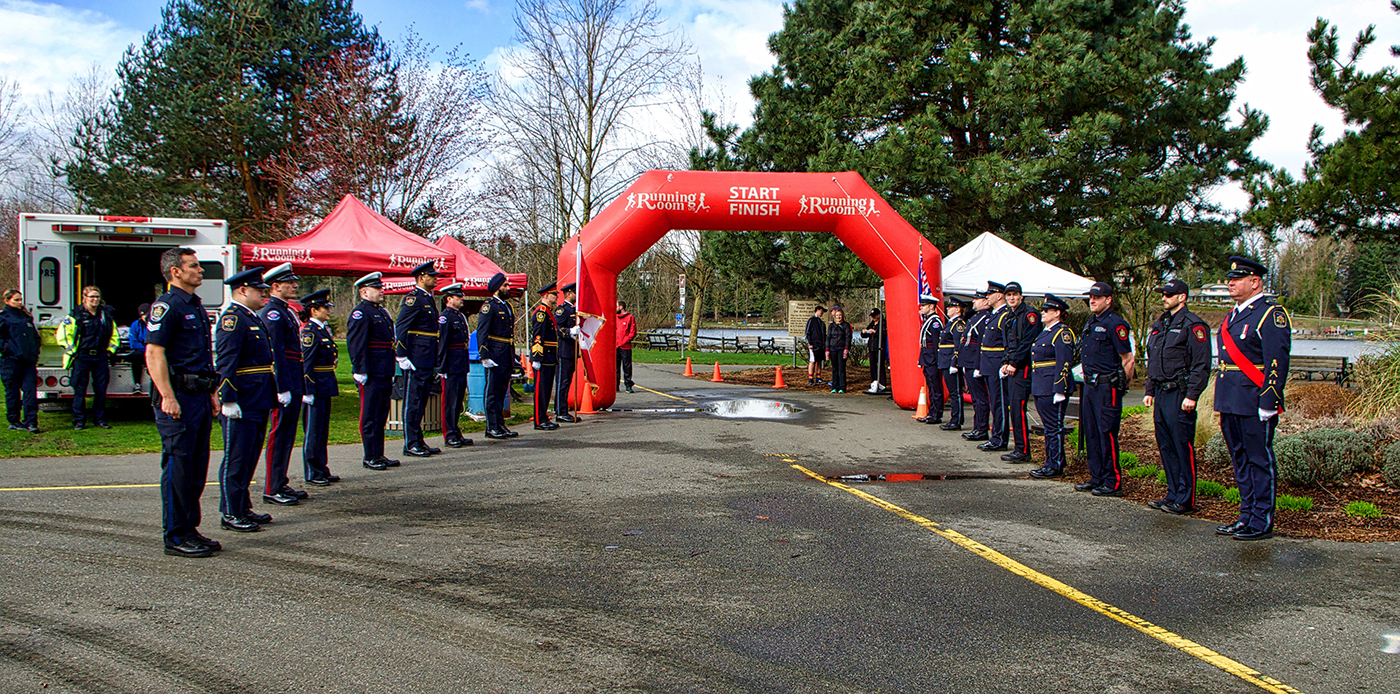A photo of local first responders, including representatives from CSC, standing at the start and finish line of the run/walk
