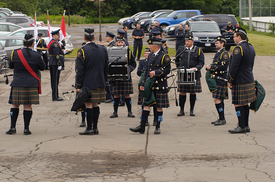 A group photo of CSC's pipes and drums members standing together in a parking lot. They are dressed in ceremonial uniforms.