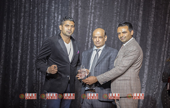 A photo of Kultar Gill receiving his Role Model of the Year Award. He is accompanied by two other men.