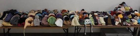 Stack of items that were made for donation, including: mittens, hats, scarves, socks, headbands and leg warmers