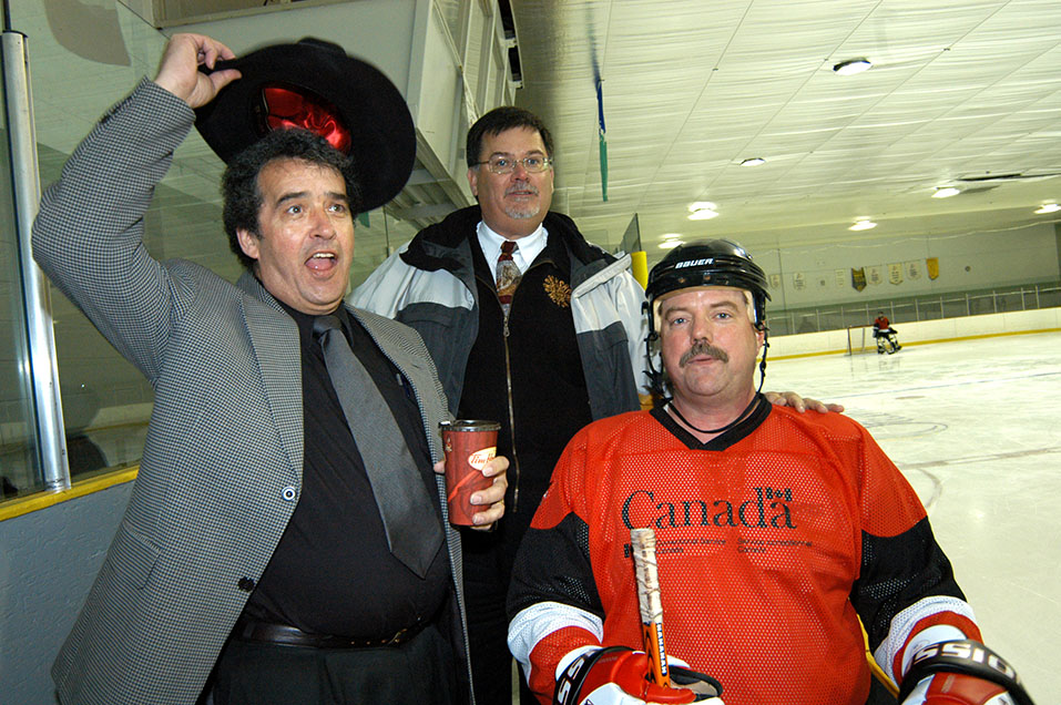 A photo of Mike dressed in hockey equipment at a charity hockey tournament. He is sitting beside CSC Commissioner Don Head and colleague Jim Murphy. Jim is waving his hat in the air.