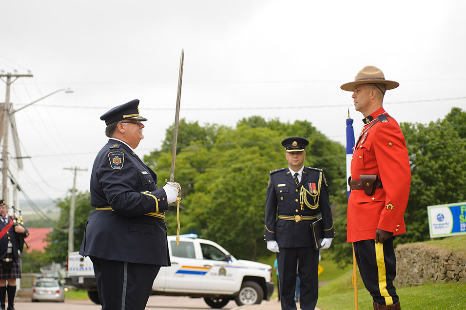 A photo of CSC Commissioner Don Head standing in front of an RCMP officer.