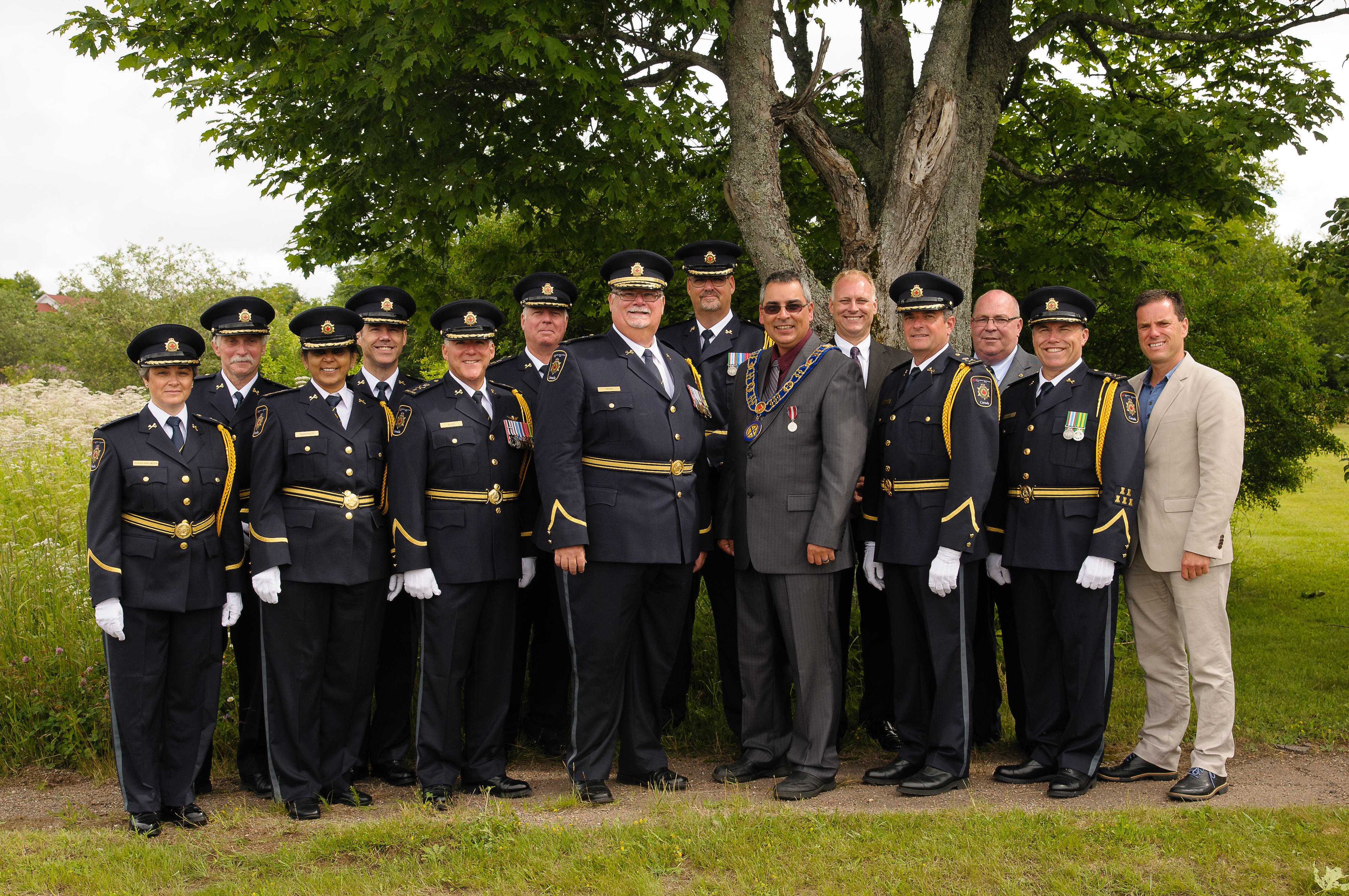 A group photo of CSC Commissioner Don Head standing with CSC employees in ceremonial uniform and the mayor of Dorchester Village.