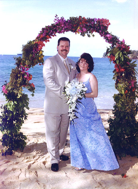 A photo of Mike with his wife Laura on their wedding day in the Caribbean. They are standing together under an arch filled with flowers on the beach.