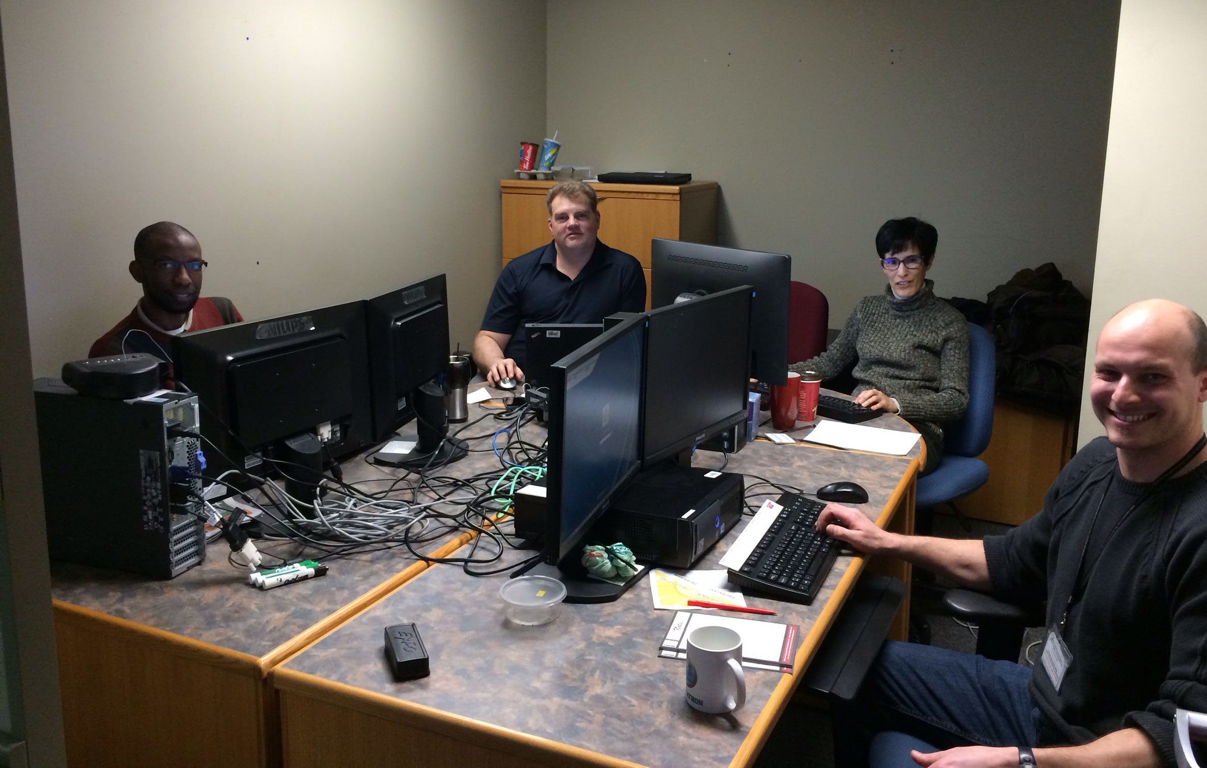 A photo of four people who participated in the code sprint to develop and tweak the new Parole Officer Dashboard. They are sitting around a table covered in computers.