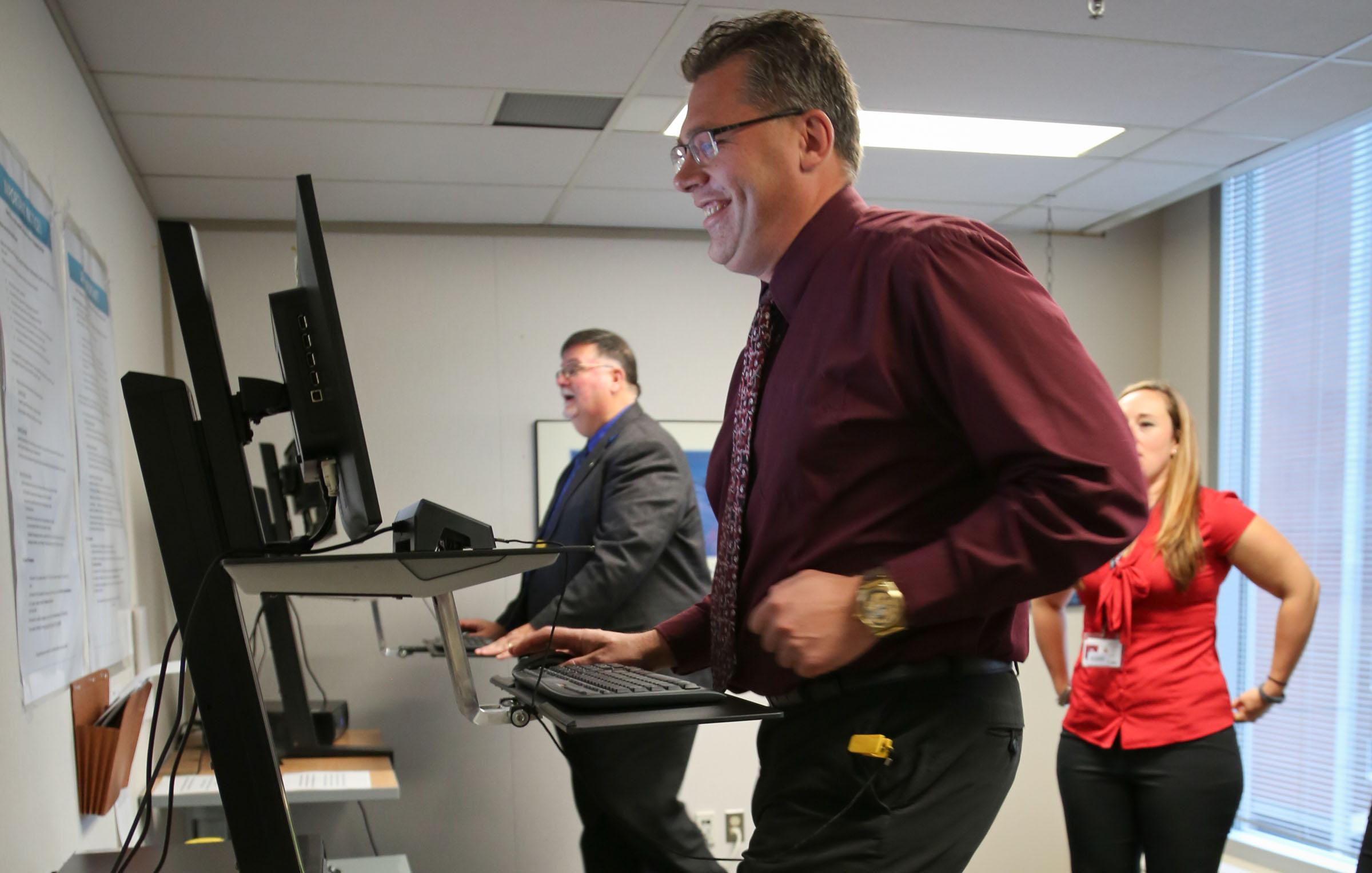 Une photographie du commissaire Don Head (à l'arrière) et de Scott Harris, commissaire adjoint, Communications et engagement, faisant l'essai des tapis roulants lors du lancement des postes de travail avec tapis roulants.