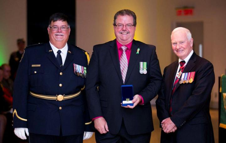 A photo of Mike standing in between CSC Commissioner Don Head and Governor General David Johnston. Mike is holding his exemplary service medal for thirty years of service.