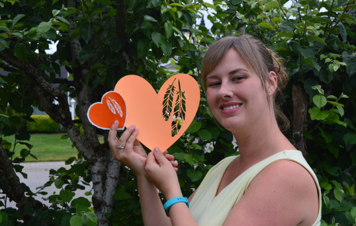 Eva Goldthorp holds the orange vinyl and paper hearts she created.