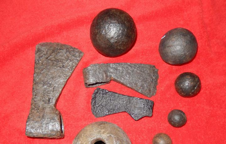 A photo of a collection of cannonballs and trade axes.