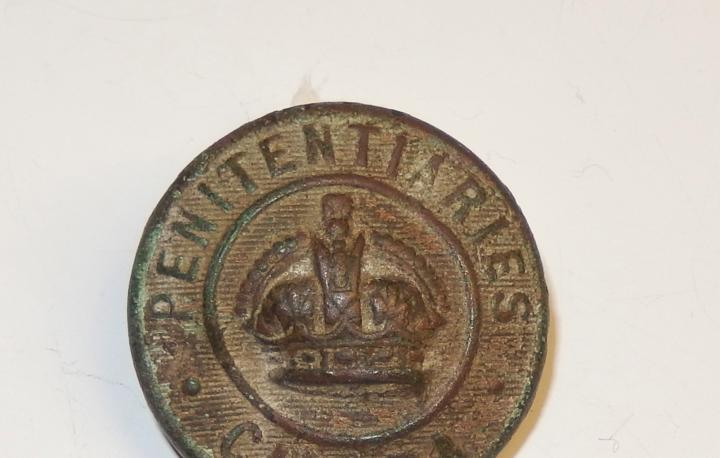 A photo of a Correctional Officer button from Penitentiaries Canada. This would have been worn by some of the first officers at Dorchester Penitentiary in the late 1800s.