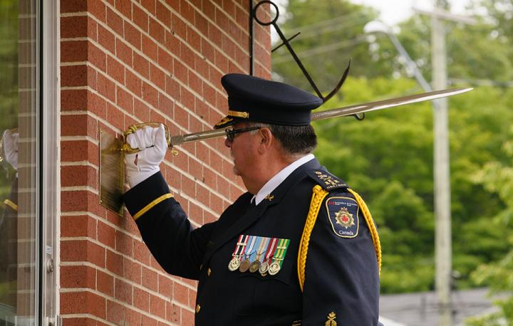 A photo of CSC Commissioner Don Head performing the ceremonial task of making dents in a plaque at city hall with the handle of his sword.