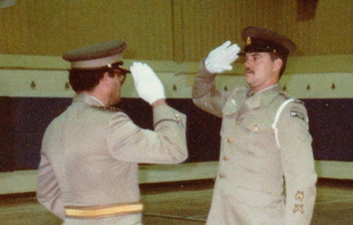 A photo of Mike at his correctional officer training graduation ceremony in 1984. He is wearing a CSC uniform and is saluting another officer.