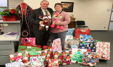 A photo of Ontario Regional Deputy Commissioner, Mike Ryan, with Tracey Augustyn. They are standing with a pile of wrapped Christmas gifts.