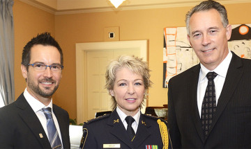 A photo of Senior Deputy Commissioner Anne Kelly standing in between Martin Gagnon and Dr. Jeremy Mills. She is wearing her ceremonial uniform.