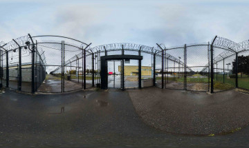 A panoramic photo of gates and barbed wire leading into a federal institution.