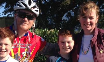 Une photo de Nicholas qui se tient au côté de Liam, un jeune survivant du cancer, et sa mère et son frère. Nicholas porte des vêtements de cyclisme et il tient son vélo.
