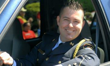 Photo de Jason portant son uniforme de cérémonie du SCC. Il est assis dans le siège du conducteur d'un véhicule stationné, la main sur le volant.