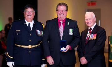 Photo de Mike debout entre le commissaire du SCC, Don Head, et le gouverneur général, David Johnston. Mike tient sa médaille pour services distingués – 30 ans de service.
