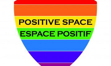 Une photographie du logo d'Espace positif. Il s'agit d'un bouclier aux couleurs de l'arc en ciel.