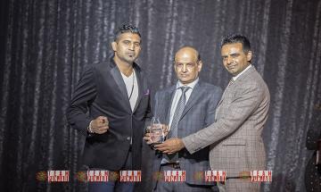 Une photo de Kultar Gill qui reçoit le prix de personnalité exemplaire de l'année. Il est accompagné de deux autres hommes.