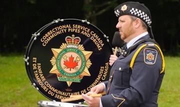 Photo d'un membre du Corps de cornemuses et de tambours du SCC jouant du tambour pendant un défilé.