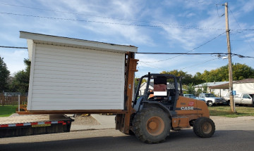 Shed being pulled on the back of a trailer.