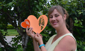 Eva Goldthorp tient les cœurs de vinyle et de papier orange qu'elle a créés.