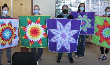 Photographiées tenant des couvertures étoilées, de gauche à droite : Christina Jocko, Janice Durham, Shirley Buffalo Calf, Charlene Wilson et Carly Shaver.