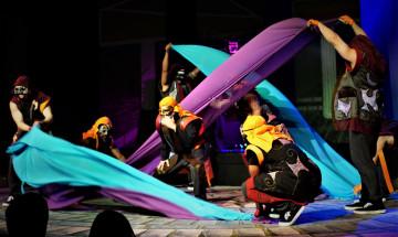 Les membres de la production théâtrale, Antigone, en costume sur scène.