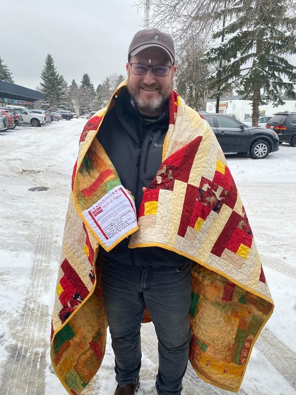 John Croucher is wrapped in a quilt that was handmade and personalized from Quilts of Valour™.